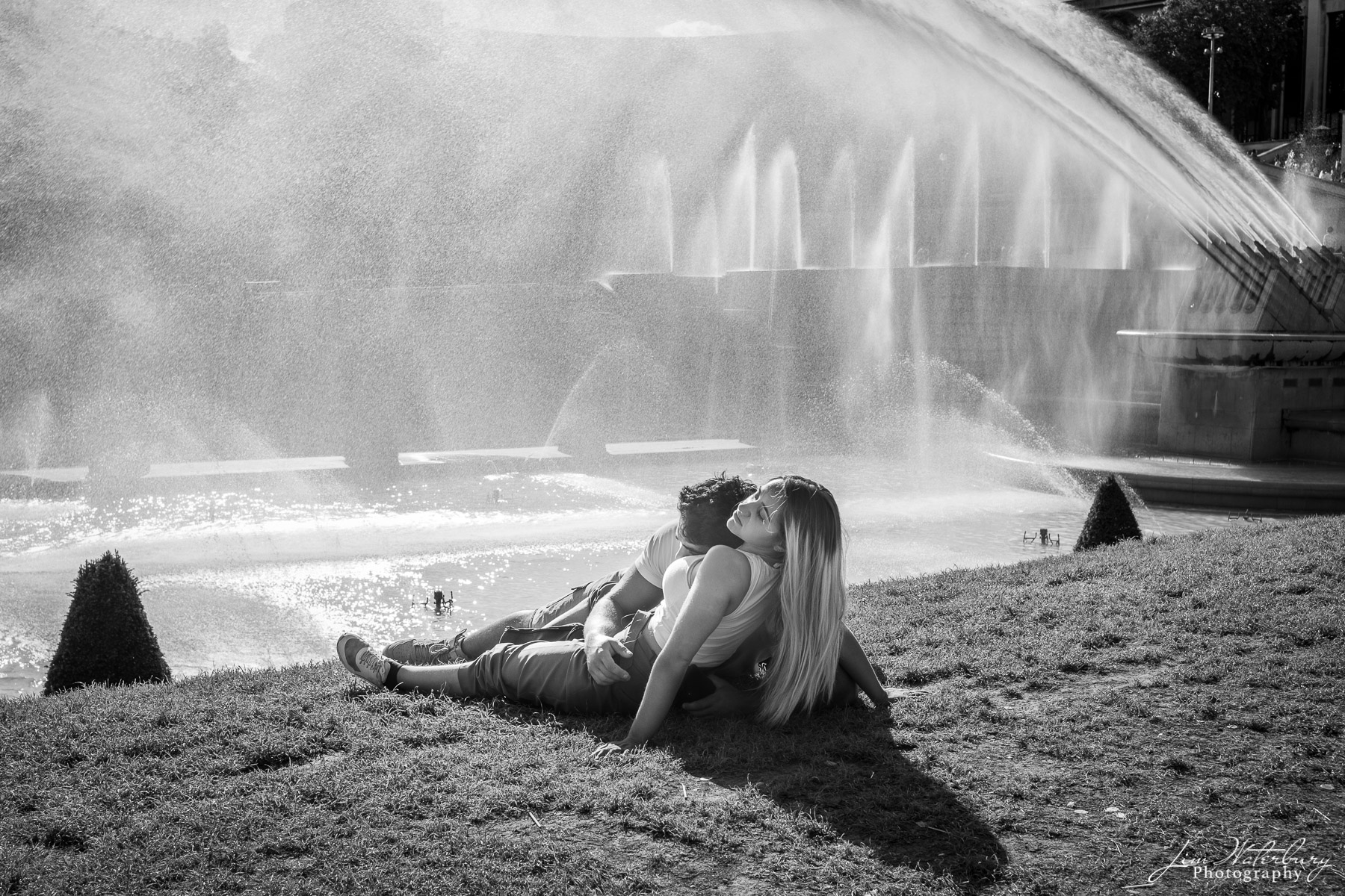Young couple relaxes on the grass bordering the pools and fountains of Place du Trocadero, Paris 1e.  Black & white.