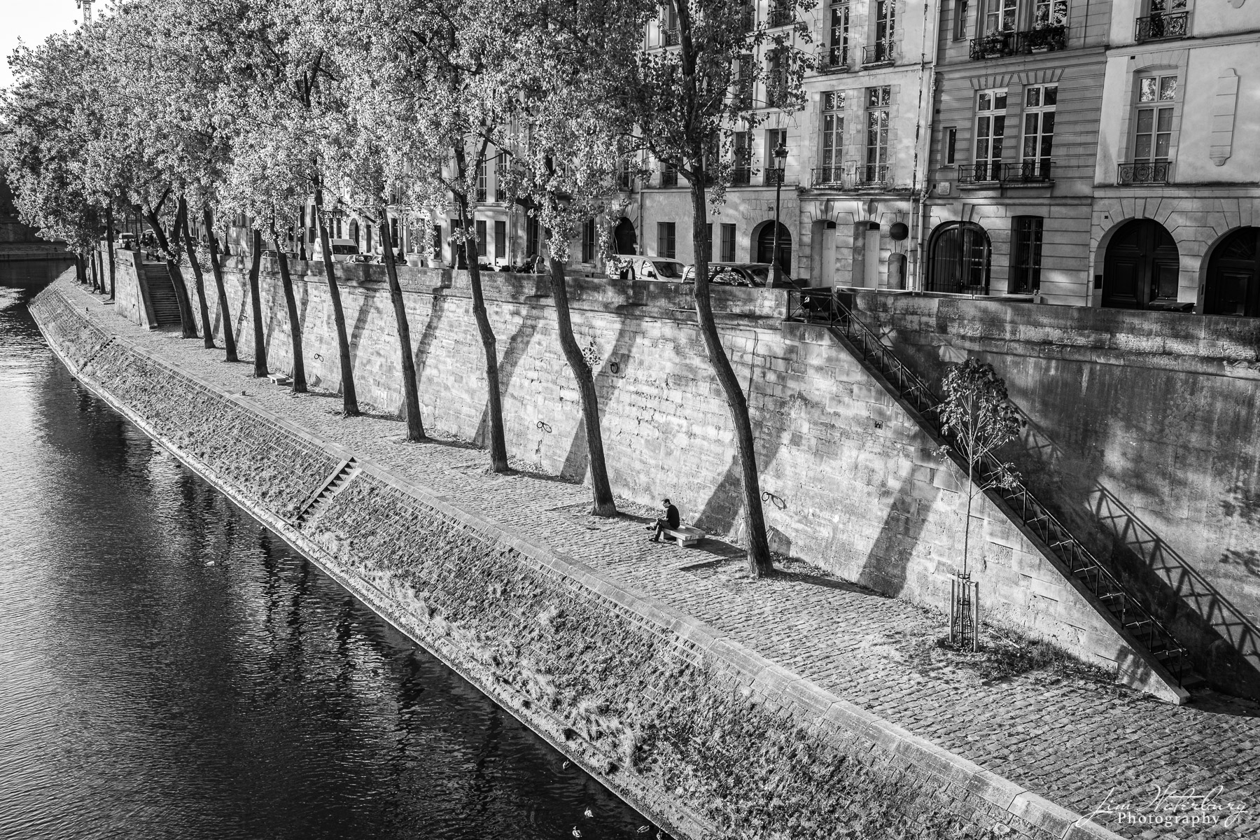A lone gentlemen relaxes on a bench along the quai of the Seine on Ile St. Louis, Paris. Black & white.