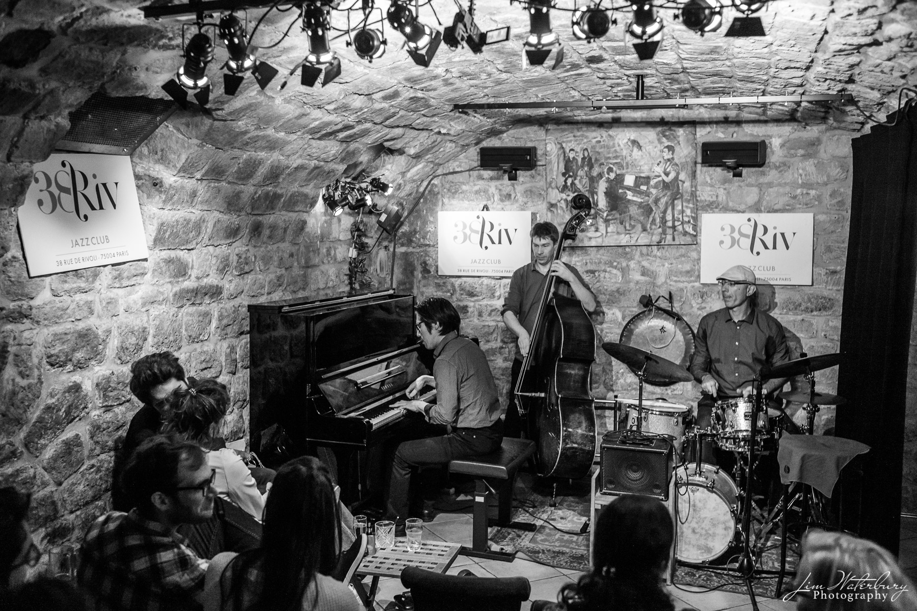 A trio plays late night jazz at the 38 Riv Jazz Club, Paris.  Black & white.