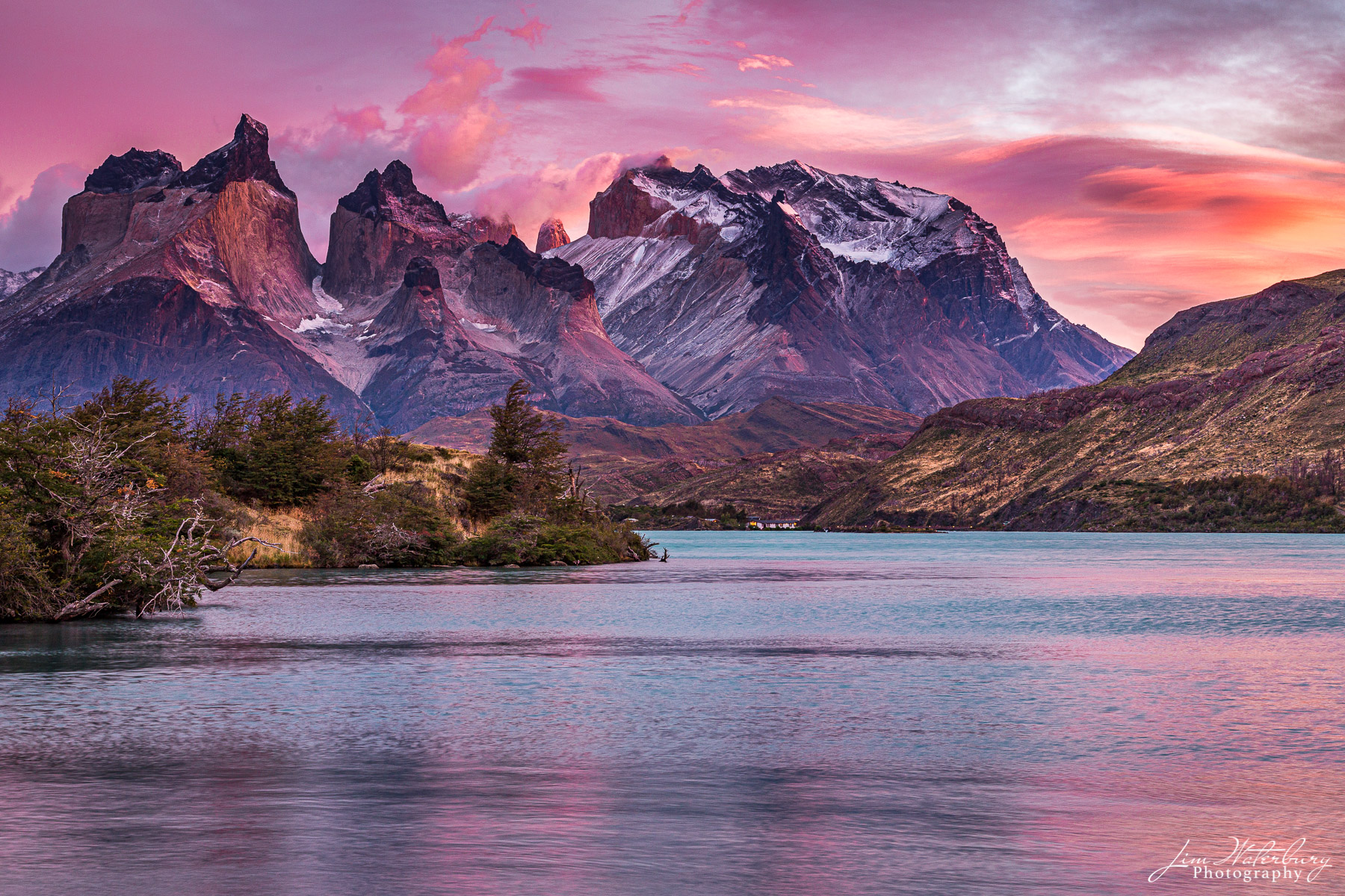 Torres del Paine,  bathed in a colorful, fall sunrise, and Pehoe Lake in the foreground, in Patagonia.