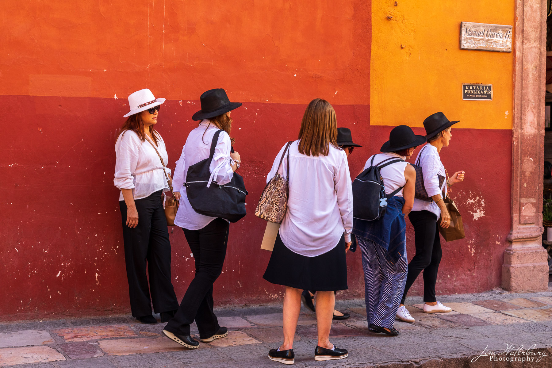 Tourists,, in white and black hats, congregate in central San Miguel.