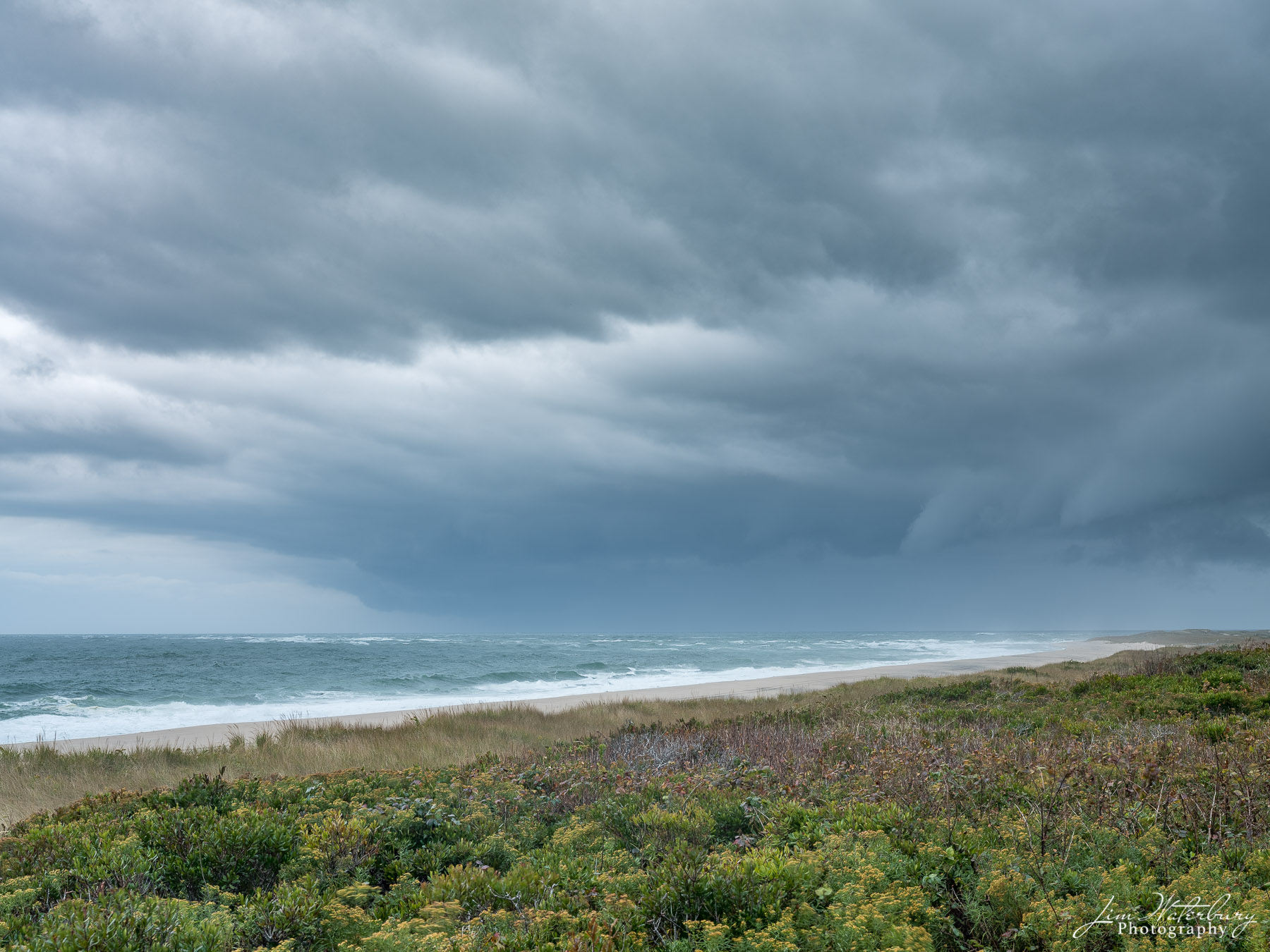 A view of the ocean from above the dunes, with a fall storm approaching from the west.