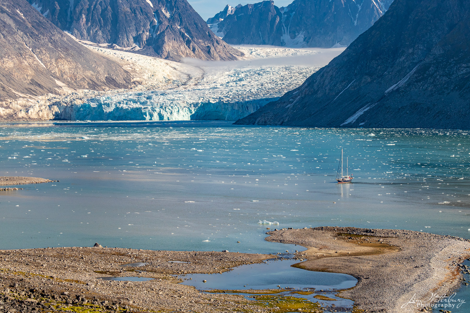 A sailboat cruises the high arctic n the waters of the Magdalene fjord, Nordvest-Spitsbergen National Park, Svalbard.