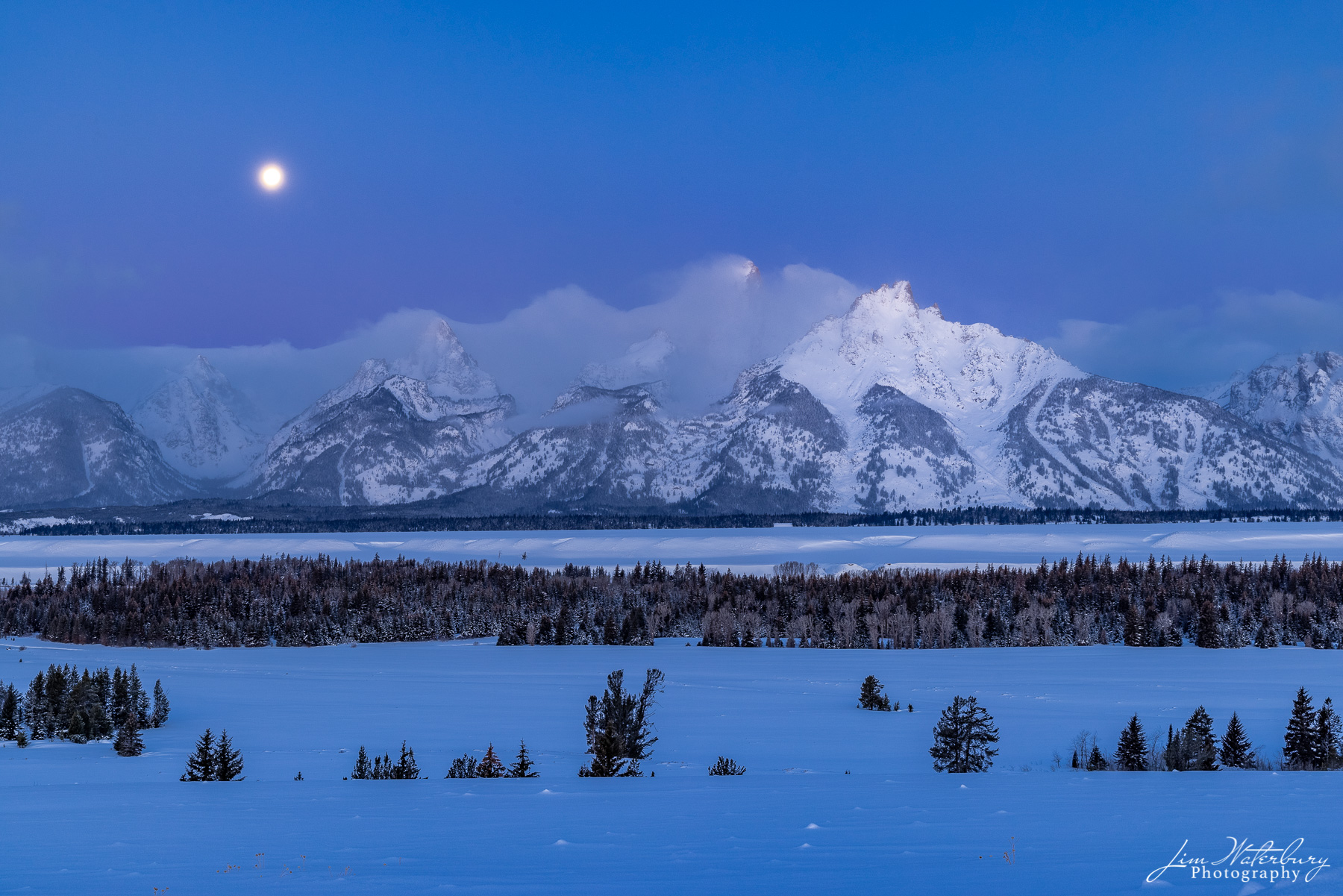 """Teton Range, in the pre-dawn light, with the full """"snow"""" moon of February about to set."""
