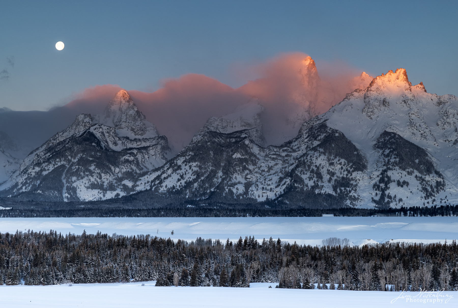 """Alpenglow on the Teton Range at sunrise, as the full """"Snow"""" moon of February sets."""