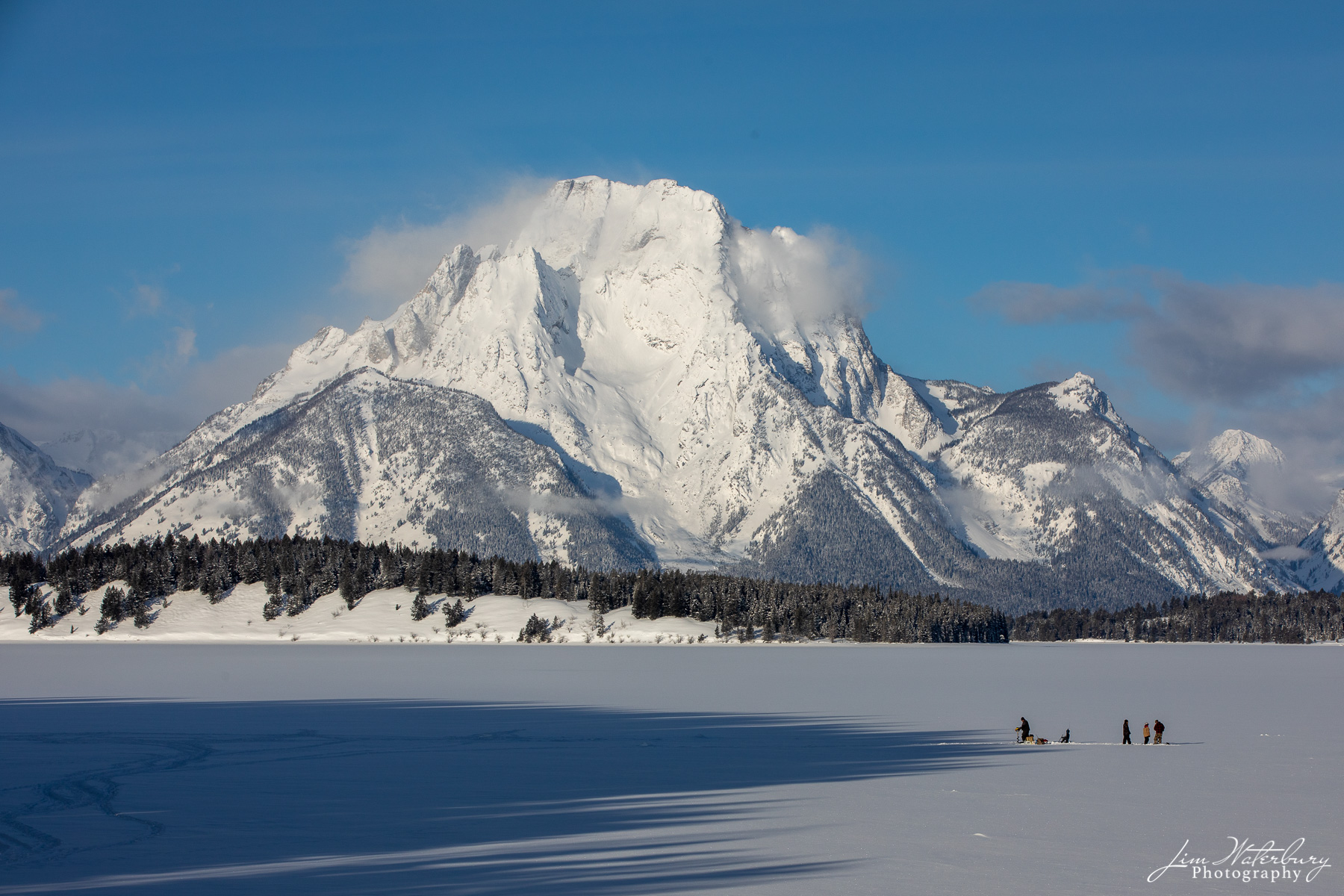 With Mt Moran in the background, hearty locals prepare to go ice fishing on Jackson Lake, Grand Teton National Park.