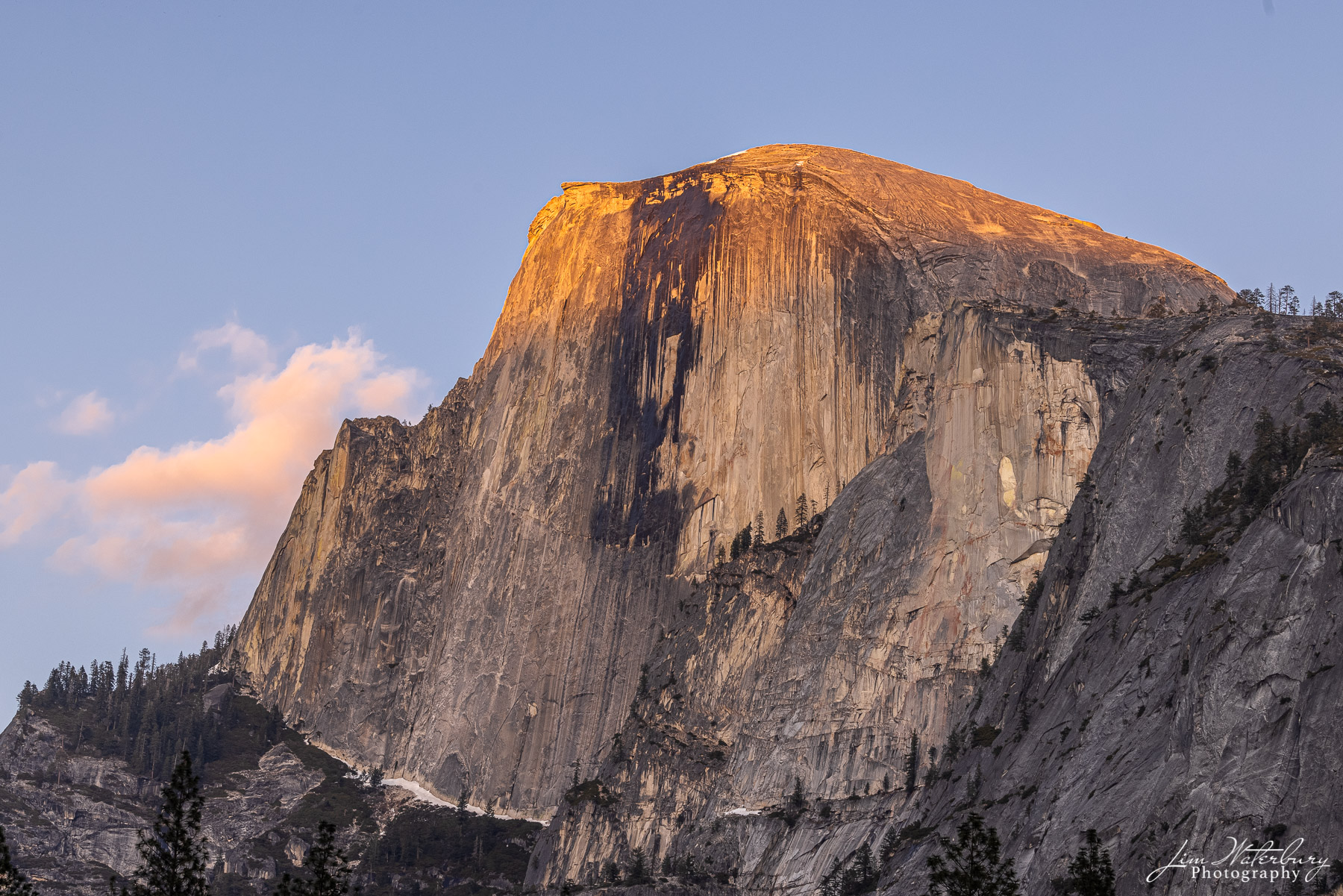 Half Dome, with the last warm light of the day hitting the peaks and lighting up nearby clouds.
