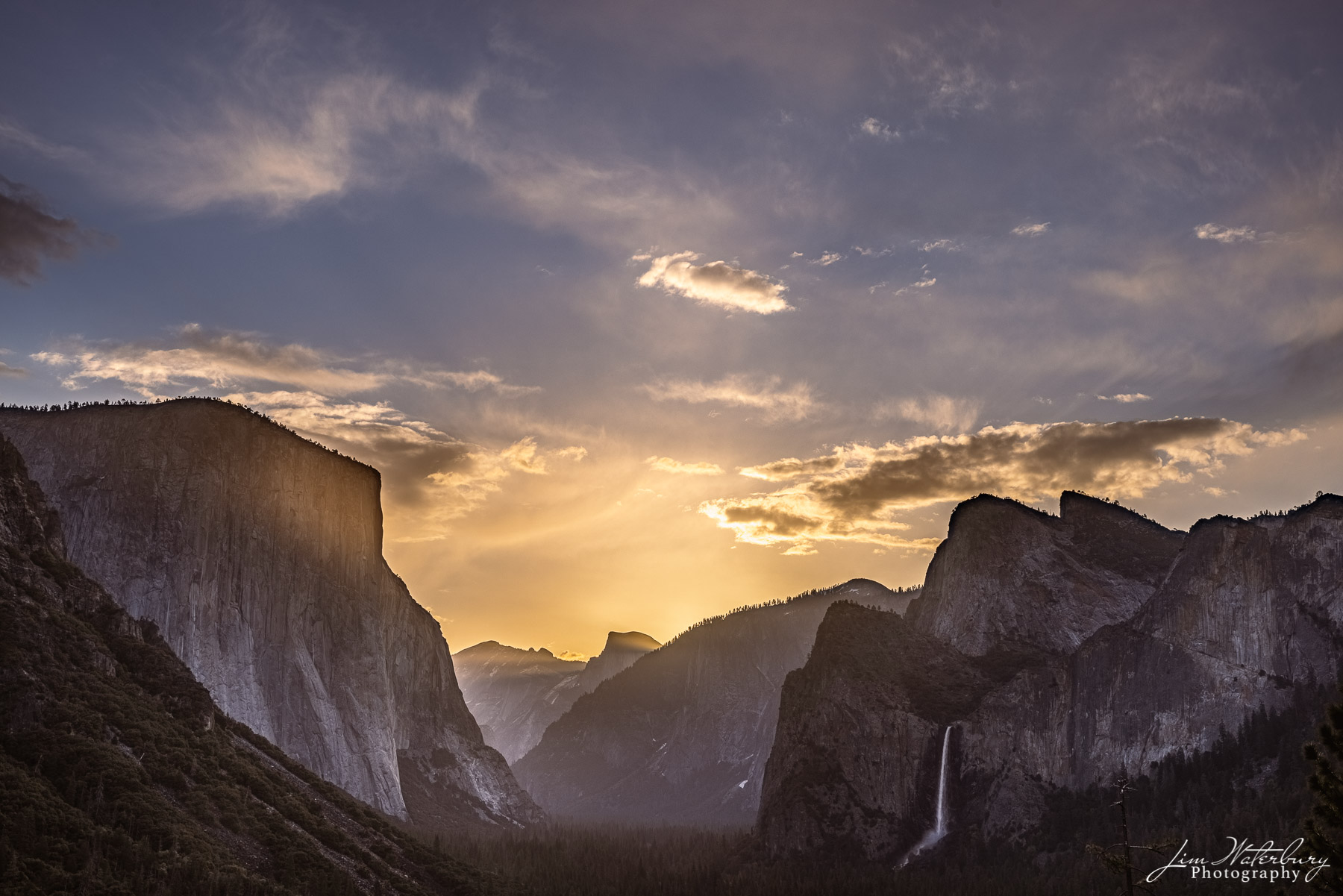 The glow of the rising sun begins to illuminate Yosemite Valley, as seen from Inspiration Point (Tunnel View).
